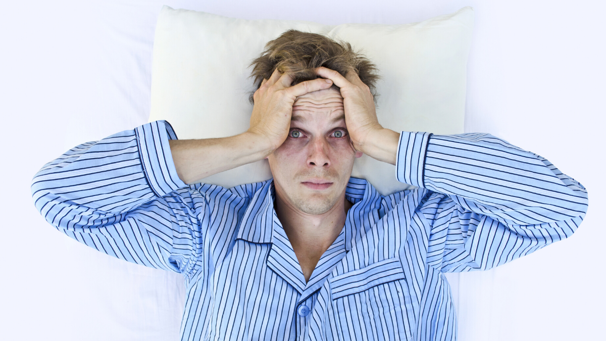 man lying awake trying to sleep